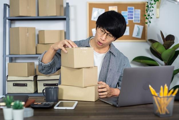 Homem de negócios asiático startup pme empreendedor ou freelance trabalhando em uma caixa de papelão prepara a caixa de entrega para o cliente