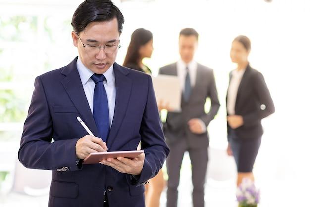 Homem de negócios asiático trabalhando com equipe