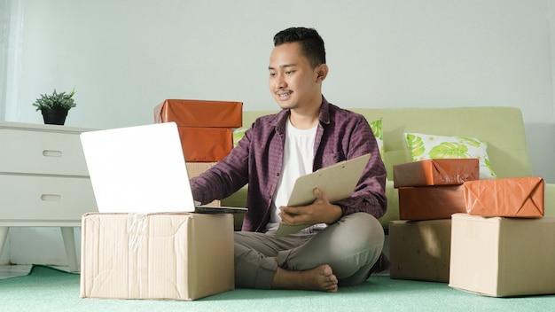 Homem de negócios asiático trabalhando com laptop em casa
