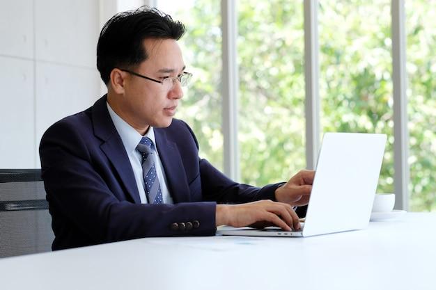 Homem de negócios asiático trabalhando com o computador portátil no escritório