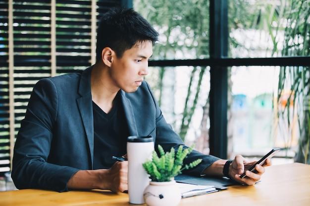 Homem de negócios asiático trabalhando em casa. empresário usando videochamada telefone inteligente com colegas
