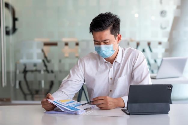 Homem de negócios asiático trabalhando usando documentos e tablet no escritório. use uma máscara para prevenir germes.