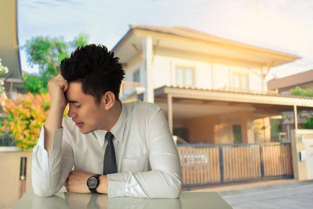 Homem de negócios asiático triste sentado ou negócio de estreito
