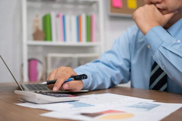 Homem de negócios asiático usa uma calculadora para calcular receitas e despesas de lucros e perdas para o relatório anual de resumo.