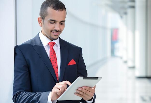 Homem de negócios asiático, usando a tabuleta, estando no escritório.