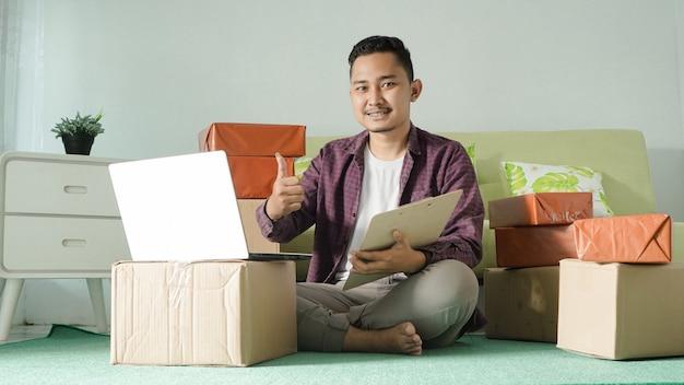 Homem de negócios asiático usando laptop e gesticulando ok em casa