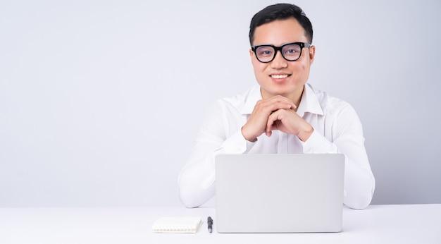 Homem de negócios asiático usando laptop em branco