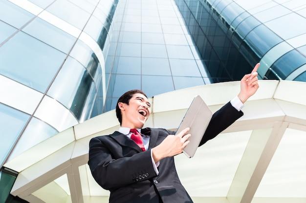 Homem de negócios asiático verificando e-mails externos em um tablet em frente ao prédio da torre