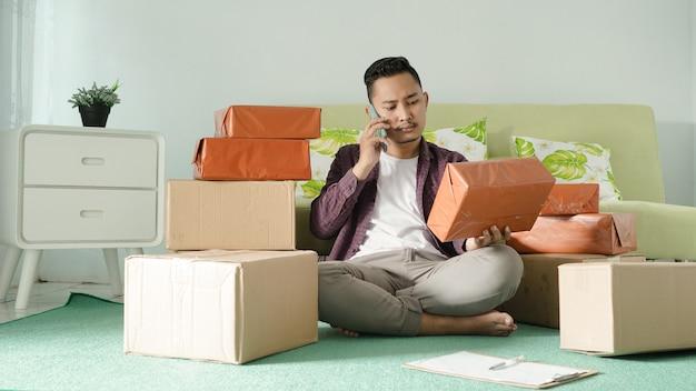 Homem de negócios asiático verificando pedidos por telefone