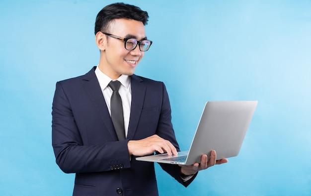 Homem de negócios asiático vestindo terno e usando laptop na parede azul