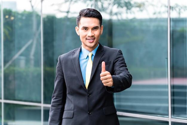 Homem de negócios asiáticos andando na frente do prédio
