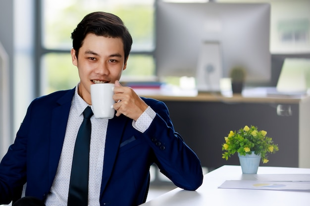Homem de negócios asiáticos atraente jovem vestindo terno azul marinho com camisa branca e gravata, sentado na cadeira executiva, bebendo café no escritório com iluminação natural.