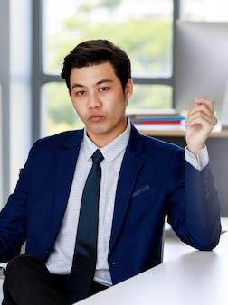 Homem de negócios asiáticos atraente jovem vestindo terno azul marinho com camisa branca e gravata, sentado na cadeira executiva, fazendo careta confiante no escritório com iluminação natural.