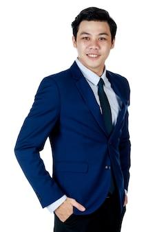 Homem de negócios asiáticos atraente jovem vestindo terno azul marinho com gravata e camisa branca virar as mãos de 45 graus nos bolsos, sorrindo em fundo branco. isolado