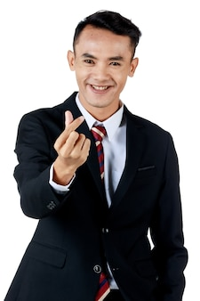 Homem de negócios asiáticos atraente jovem vestindo terno preto com camisa branca e gravata, fazendo a pose de mini coração e sorrindo e parecendo confiante. fundo branco. isolado