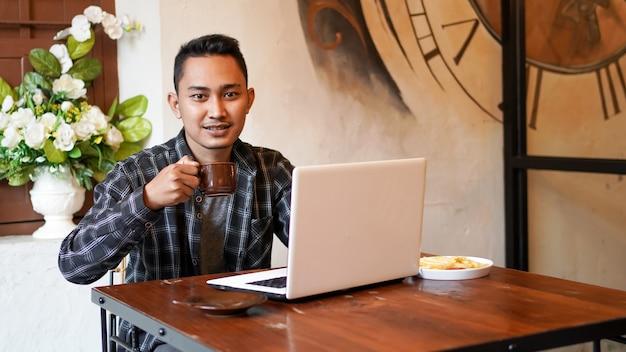 Homem de negócios asiáticos bebendo café trabalhando com um laptop no café