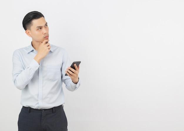 Homem de negócios asiáticos bonito jovem segurando um smartphone preto e pensando em uma idéia enquanto olha para cima