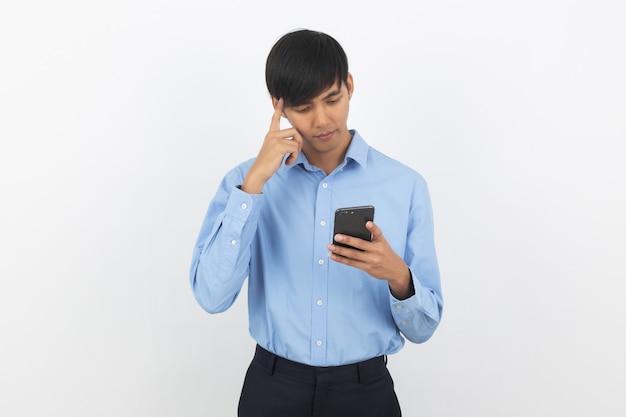 Homem de negócios asiáticos bonito jovem segurando um smartphone preto e pensando em uma idéia