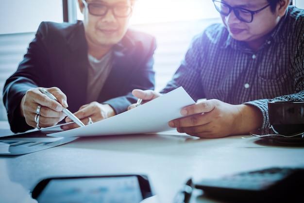 Homem de negócios asiáticos de meia-idade discuta problemas e oportunidades para o crescimento dos negócios.