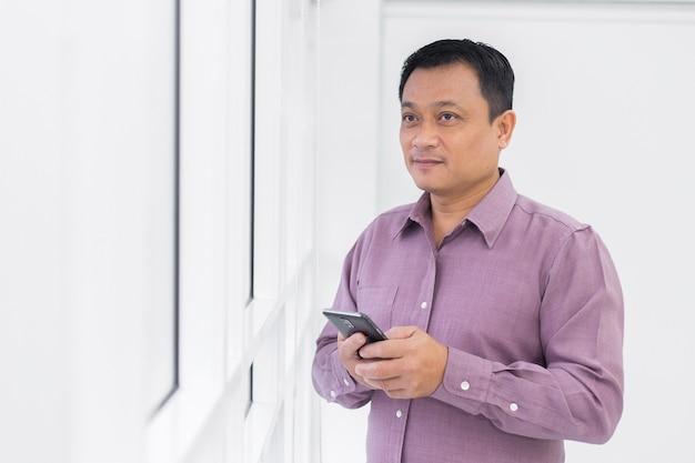 Homem de negócios asiáticos de meia idade segurando um smartphone na mão
