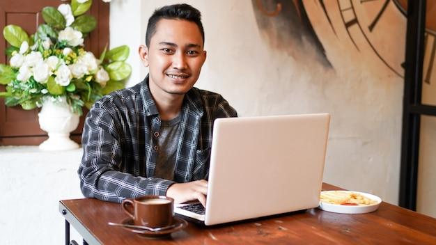 Homem de negócios asiáticos digitando em um laptop em um café