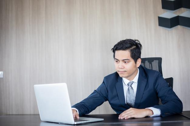 Homem de negócios asiáticos e grupo usando o notebook para reunião e homens de negócios sorrindo feliz por trabalhar