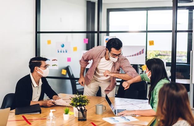 Homem de negócios asiáticos e mulher em quarentena por coronavírus usando máscara protetora tremendo com os cotovelos em normalidade com grupo de reunião de negócios profissional e discutindo estratégia no escritório