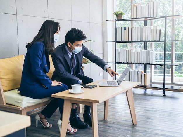 Homem de negócios asiáticos e mulher usando terno e máscaras protetoras usando o computador na mesa