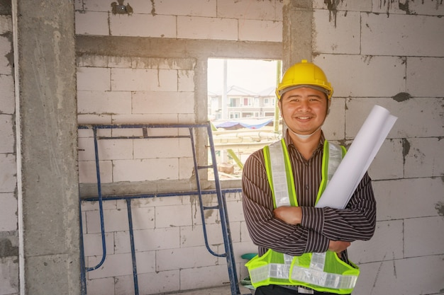 Homem de negócios asiáticos engenheiro de construção trabalhador com capacete protetor e projetos de papel disponível no local de construção da casa