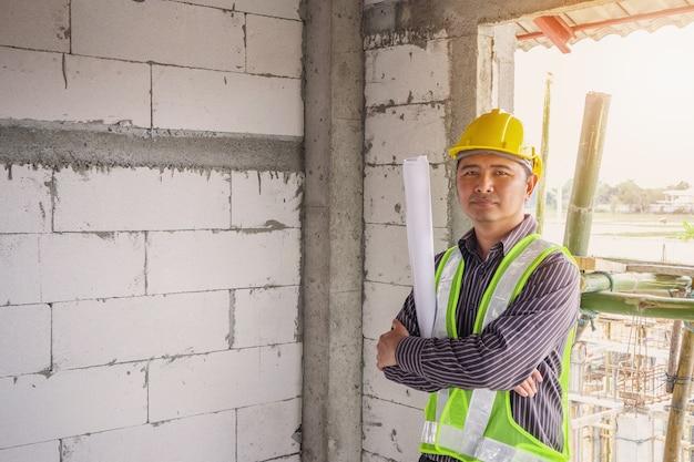 Homem de negócios asiáticos engenheiro de construção trabalhador com capacete protetor e projetos de papel disponível no local de construção