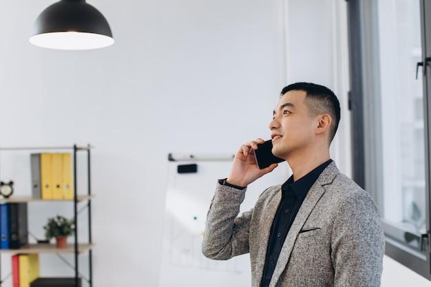 Homem de negócios asiáticos falando no celular no escritório moderno apartamento