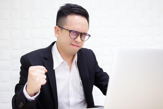 Homem de negócios asiáticos infeliz sofre de trabalhar duro por um longo tempo.