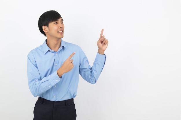 Homem de negócios asiáticos jovens com camisa azul, apontando para o lado com um dedo para apresentar um produto ou uma ideia enquanto olha para a frente sorrindo isolado no branco