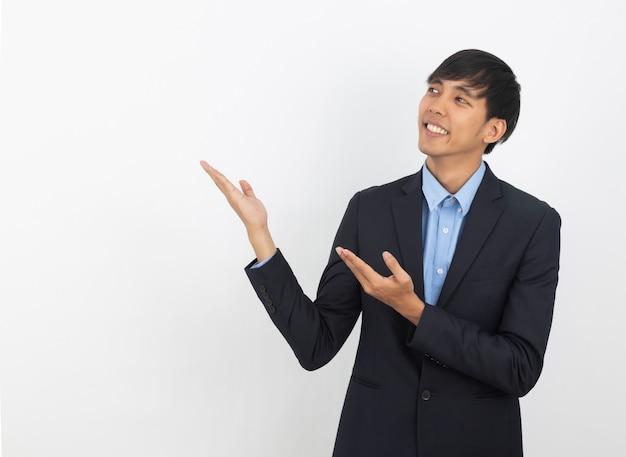 Homem de negócios asiáticos jovens com camisa azul, apontando para o lado com uma mão para apresentar um produto ou uma ideia