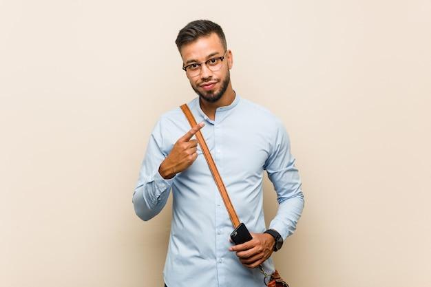 Homem de negócios asiáticos jovens de raça mista, segurando um telefone apontando com o dedo para você, como se convidando se aproximar.