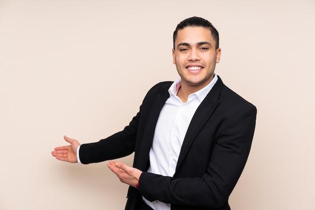 Homem de negócios asiáticos na parede bege, estendendo as mãos para o lado para convidar para vir