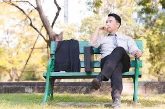 Homem de negócios asiáticos retrato sente-se em um relaxamento de cadeira de madeira verde no parque