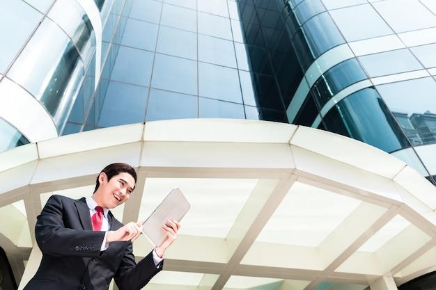 Homem de negócios asiáticos trabalhando lá fora no tablet pc