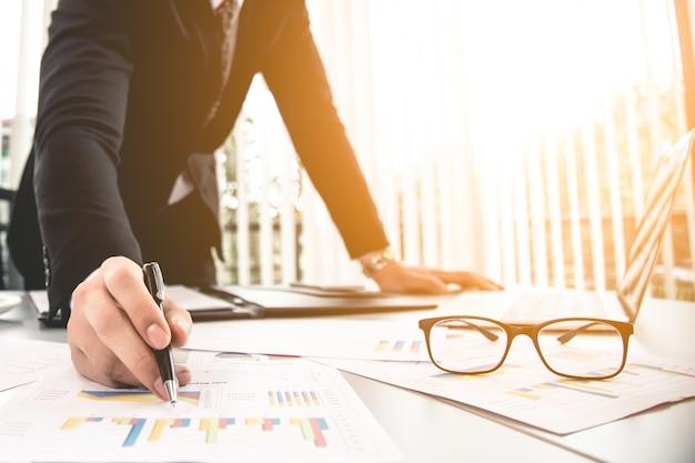 Homem de negócios asiáticos trabalhando no escritório com caneta de óculos portátil e documentos na sua mesa
