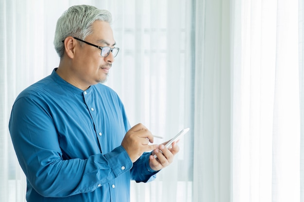 Homem de negócios asiáticos velho com cabelos grisalhos vestindo óculos e trabalhando no escritório