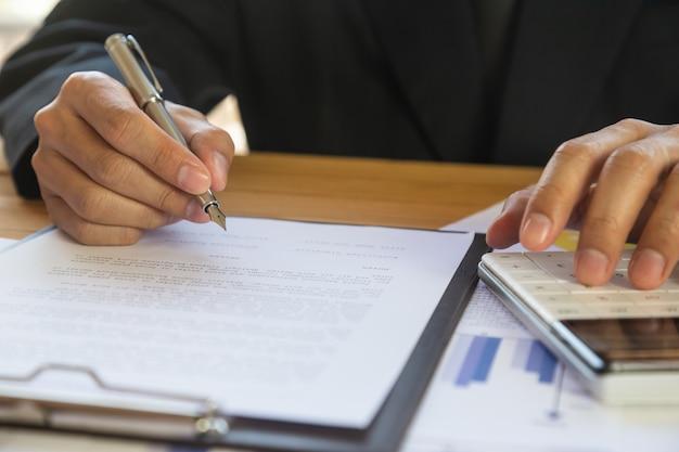 Homem de negócios, assinando um contrato. possui o sinal de negócios pessoalmente.