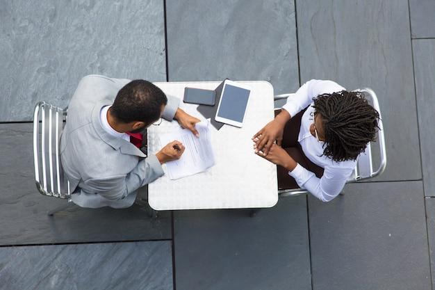 Homem de negócios, assinar documentos durante a reunião com o parceiro