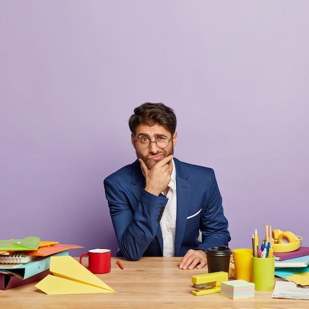 Homem de negócios atencioso sentado na mesa do escritório