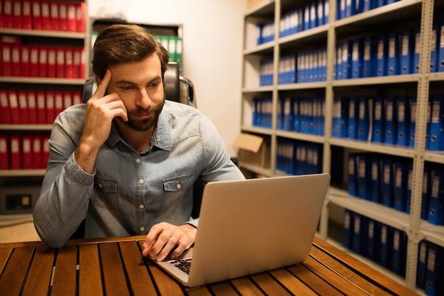 Homem de negócios atencioso usando laptop na sala de armazenamento de arquivos