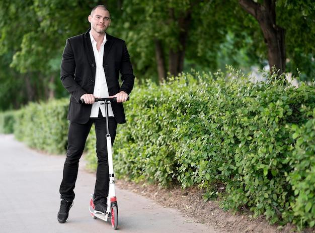 Homem de negócios ativo feliz andar de scooter ao ar livre