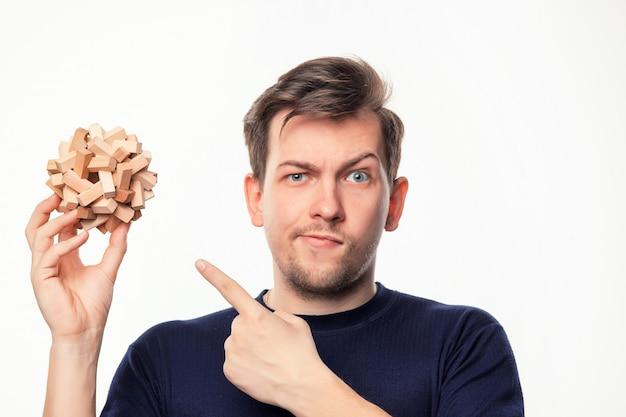 Homem de negócios atraente 25 anos olhando confuso com quebra-cabeças de madeira.