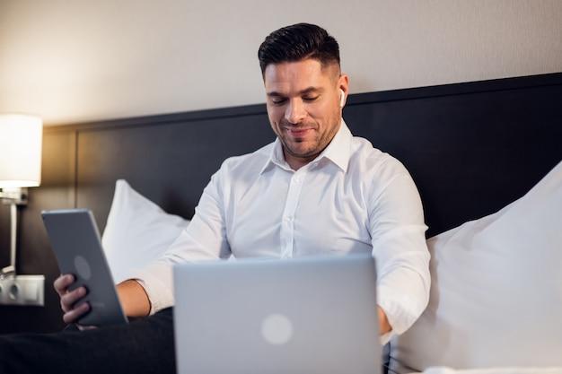 Homem de negócios atraente com seus gadgets na cama