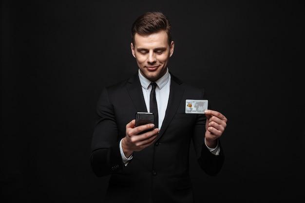 Homem de negócios atraente confiante vestindo terno isolado na parede preta, usando telefone celular, mostrando cartão de crédito de plástico