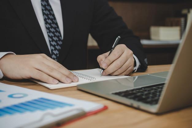 Homem de negócios atraente de terno preto, trabalhando e escrevendo no relatório do documento na mesa na sala de reuniões em casa, escritório, investimento, contrato, marketing digital digital e conceito de negócios financeiros