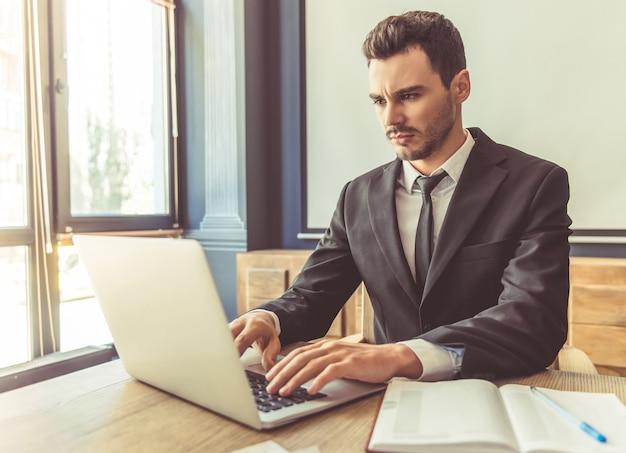 Homem de negócios atraente no terno formal está trabalhando com laptop